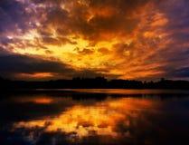 Dramatic cloudy sunset sky reflection on lake. Orange water stock photography