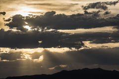 Dramatic cloudy sunset with sun rays and mountains Royalty Free Stock Photos