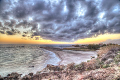 Dramatic coastal sunset or sunrise. With a view across a sandy bay to an orange glow on the horizon under a spectacular cloudscape royalty free stock image