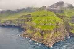 Dramatic coastline and cliffs on Faroe islands cloudy day