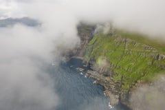 Dramatic coastline and cliffs on Faroe islands foggy day
