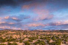 Dramatic colorful clouds at sunset over desert and mountains stock images