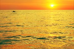 Dramatic colorful sea sunset with sun setting on water royalty free stock photography