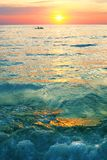 Dramatic colorful sea sunset with sun setting on water lonely boat on horison stock images