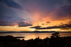 Dramatic and colorful sunset over Kvarner bay, with silhoueted trees in the foreground and the Učka mountain stock image