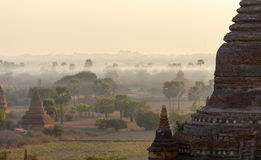 Bagan Temples in Mist at Sunrise. The dramatic colors of sunrise over Bagan with layers of morning mist filling the valleys Royalty Free Stock Photos