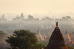 Bagan Temples in Mist at Sunrise. The dramatic colors of sunrise over Bagan with layers of morning mist filling the valleys Royalty Free Stock Images