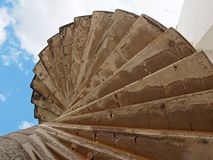 Dramatic curving concrete outdoor spiral staircase in stained brown colors against a blue cloudy sky. A dramatic curving concrete outdoor spiral staircase in royalty free stock image