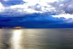 Dramatic dark cloudy sky above the sea. Stock Photos
