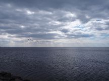 Dramatic dark cloudy sky over the sea royalty free stock photography