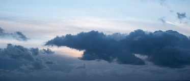 Dramatic, dark grey storm cloud in sky at dusk. Early evening with dark blue sky stock photography