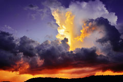 Dramatic dark purple and red storm clouds at sunset Stock Photos