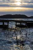 Dramatic dark sunset over wooden pier on lake in Ingared near Gothenburg, Sweden Stock Photo