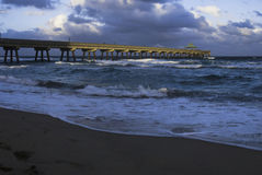 Dramatic dusk light on fishing pier and sea Stock Photos