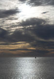 Dramatic evening seascape with sailing boat on dark sea. Or ocean water after sunset on grey cloudy sky background Royalty Free Stock Images