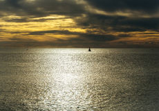 Dramatic evening seascape with sailing boat on dark sea. Or ocean water after sunset on grey and orange cloudy sky background Royalty Free Stock Image