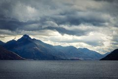 Dramatic evening sky over the mountains and lake Wakatipu. In New Zealand stock photo