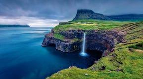 Dramatic evening view of Mulafossur Waterfall. Dark cloud on Vagar island, Gasadalur village location, Faroe Islands, Kingdom of D