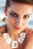 Dramatic eyes. A portrait of a beautiful brunette model wearing chunky jewelry and dramatic make-up on her dark hazel eyes royalty free stock images