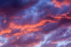 Dramatic fiery sunset sky. In a mixture of violet, pink, orange and black colors Stock Photo