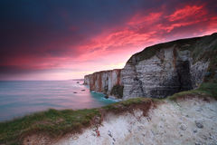 Dramatic fire sunrise over cliffs in ocean Stock Photography