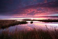 Dramatic fire sunrise over river Stock Image