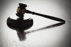 Dramatic Gavel Silhouette on Reflective Wood Stock Image