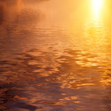 Dramatic golden sky reflected in water Royalty Free Stock Images