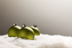 Dramatic Green Christmas Ornaments on Snow Over a Grey Background Stock Photo