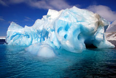 Dramatic hollowed out iceberg in sea. Hollowed out blue iceberg in sea Royalty Free Stock Photos