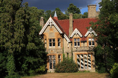 Dramatic house in the woods. A rather dramatic image of a large period family home of stone construction surrounded by woodland stock photo