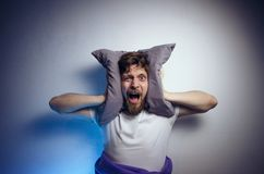 Dramatic image, man can`t sleep from the noise. Holding pillow on his ears stock photos
