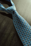 Dramatic image of necktie on the wooden table Stock Photography