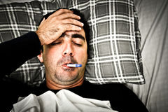 Dramatic image of a sick man in bed with fever Royalty Free Stock Photo