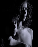 Dramatic Image of Young Man and Woman. A black and white image with dramatic lighting of a young man and woman side by side and bare shouldered Royalty Free Stock Images