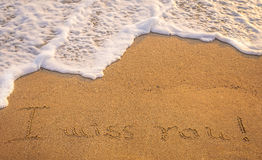 Dramatic inscription. Miss You on wet golden beach sand in sunset light Stock Image