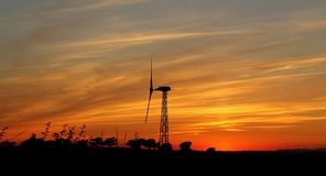 A dramatic intense orange sunset with silhouetted wind turbine and horizon stock images