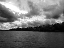 Dramatic lake sky. Black and white image of a dramatic sky over a lake, along the edge tree line. Out on a boat on the lake for fishing, when a storm or rainy Royalty Free Stock Photography