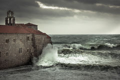 Dramatic landscape with ancient castle on sea shore during storm with big stormy waves and dramatic sky with rain in fall season o. Overcast landscape with Stock Photo