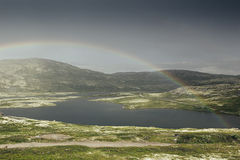 Dramatic landscape with beautiful rainbow over arctic meadows, mountain and lake. Stock Photo