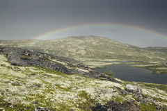 Dramatic landscape with beautiful rainbow over arctic meadows, mountain and lake. Royalty Free Stock Image