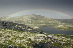 Dramatic landscape with beautiful rainbow over arctic meadows, mountain and lake. Royalty Free Stock Images