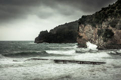 Dramatic landscape with cliffs on sea shore during storm with big stormy waves and dramatic sky with rain in fall season on sea co Stock Photo