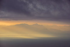 Dramatic landscape view of sunrise over mountains and the ocean Stock Images