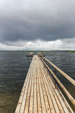 Dramatic landscape with wooden pier and fishermen Royalty Free Stock Photos