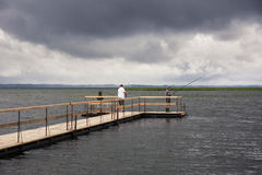 Dramatic landscape with wooden pier and fishermen Stock Photo