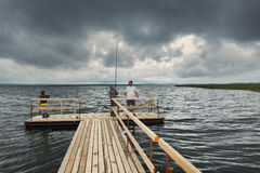 Dramatic landscape with wooden pier and fishermen Stock Images