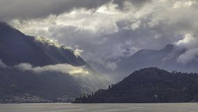 Dramatic lansdcape on Lake Como. Sun rays pass trough the clouds as storm approaches Lake Como royalty free stock image