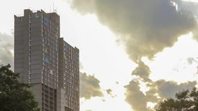 Dramatic late afternoon clouds break to reveal sun rays behind a tight shot of colorful unique high rise apartment buildings 4K UH. A dramatic timelapse of stock video