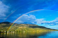 Late Afternoon Rainbow Over Gulf of Corinth Bay, Greece. Dramatic late afternoon light after rainstorm with a colourful rainbow and dark clouds above, and royalty free stock photo